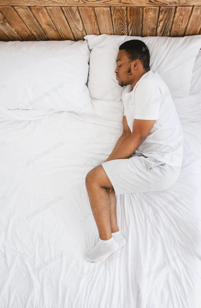 African American Guy Sleeping Lying In Bed At Home, Top-View