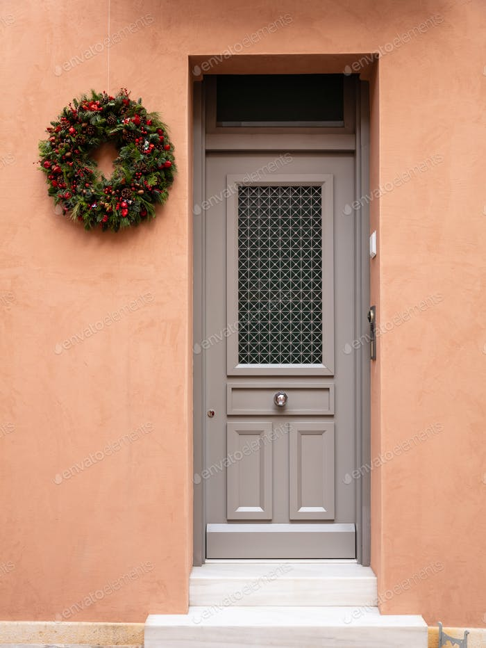 Christmas wreath decoration. Wooden entrance door in old town of Plaka, Athens Greece.