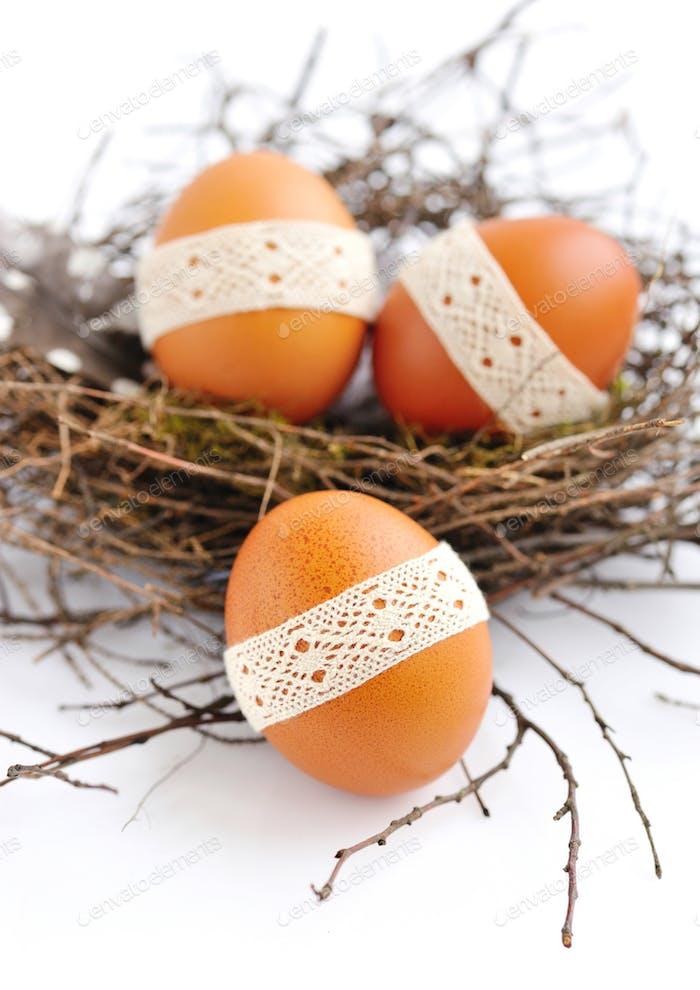 Nest mit Ostereiern auf weißem Hintergrund