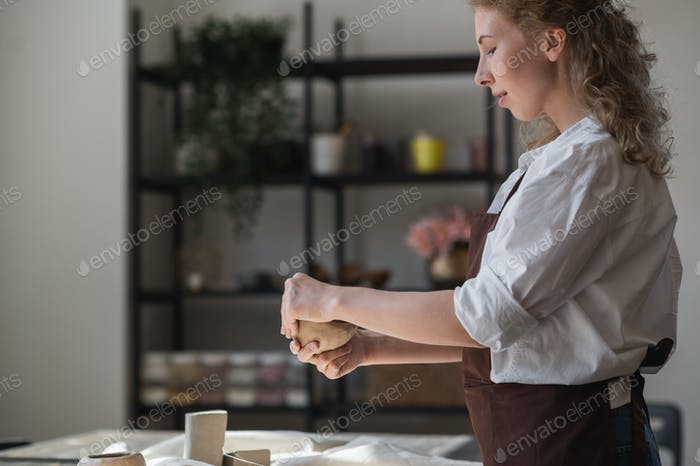 A young potter woman making pot in her own working place. Standing in spacious studio creating the