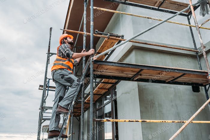 handsome builder climbing on scaffolding at construction site