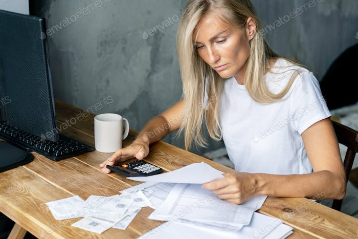 A blonde woman sits at a desk and works with documents. Counting financial expenses and income