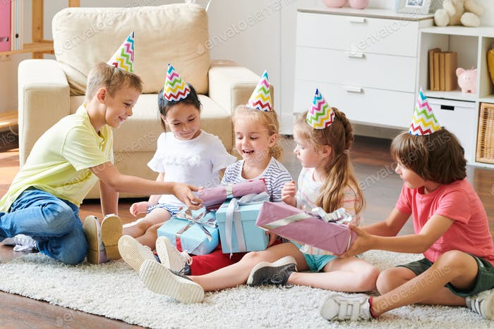 Group of adorable friends in birthday caps giving presents to happy blonde girl