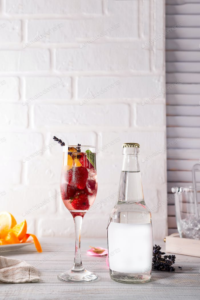 alcohol cocktail with fresh fruits and berries with a bottle of tonic and a place