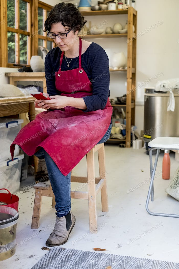 Woman wearing red apron sitting on stool in her ceramics workshop, checking her mobile phone.
