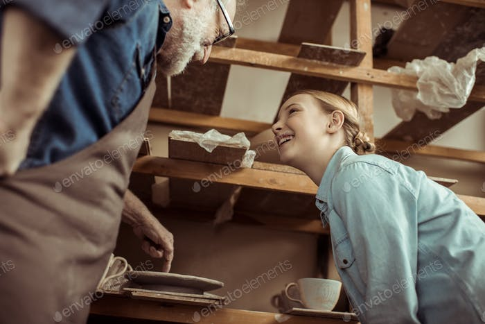 Grandfather Explaining To Granddaughter How To Use Pottery Wheel