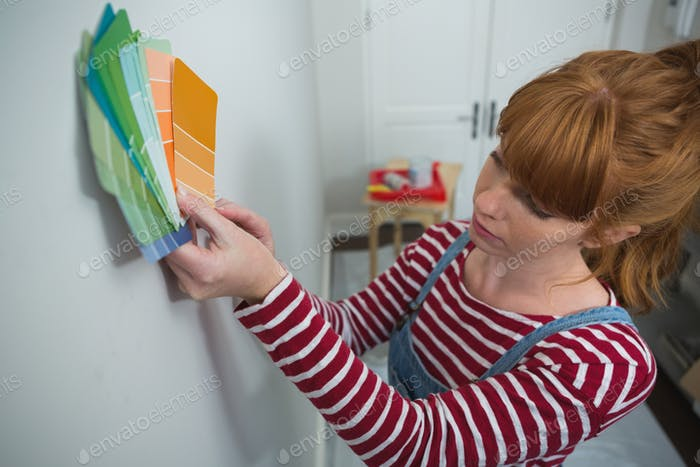 Female painter matching color shades at home