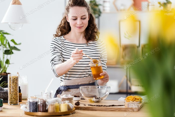 Smiling woman pouring honey
