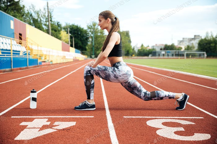 Woman athlete working out on stadium