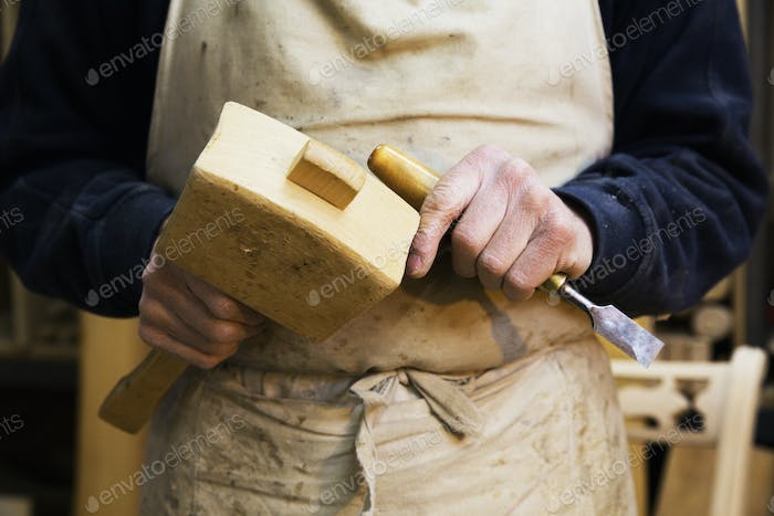 Close up of a man in a carpentry workshop, holding a wooden mallet and chisel.