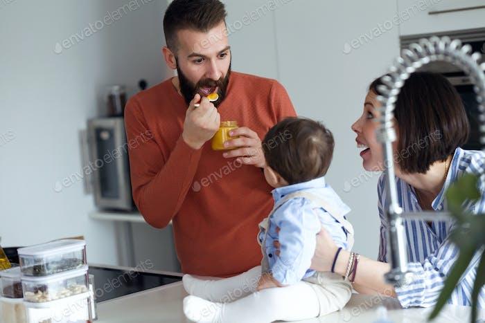 Hübsche junge Eltern füttern sie Babybrei in der Küche zu Hause.