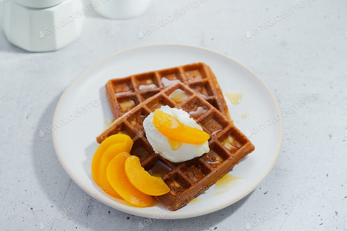 Sweet Homemade Belgian Waffle with honey, peaches in syrup, whipped cream in plate.