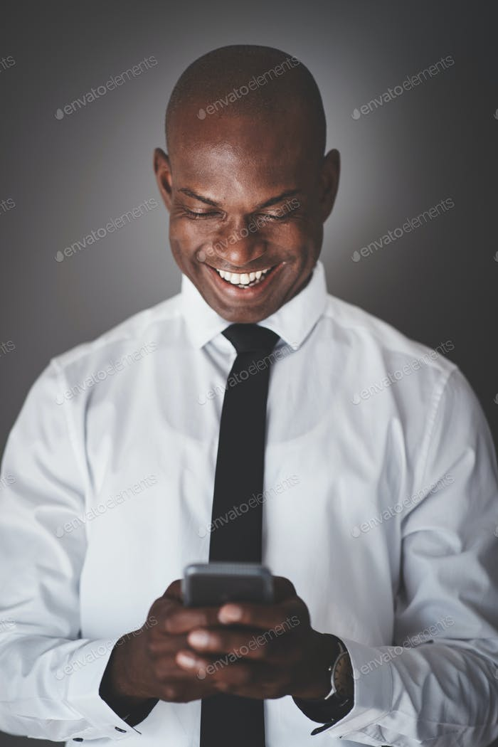 Smiling African businessman using his cellphone against a gray background