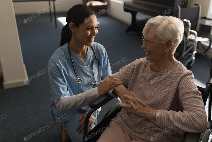 Front view of happy female doctor talking with disable senior woman at nursing home