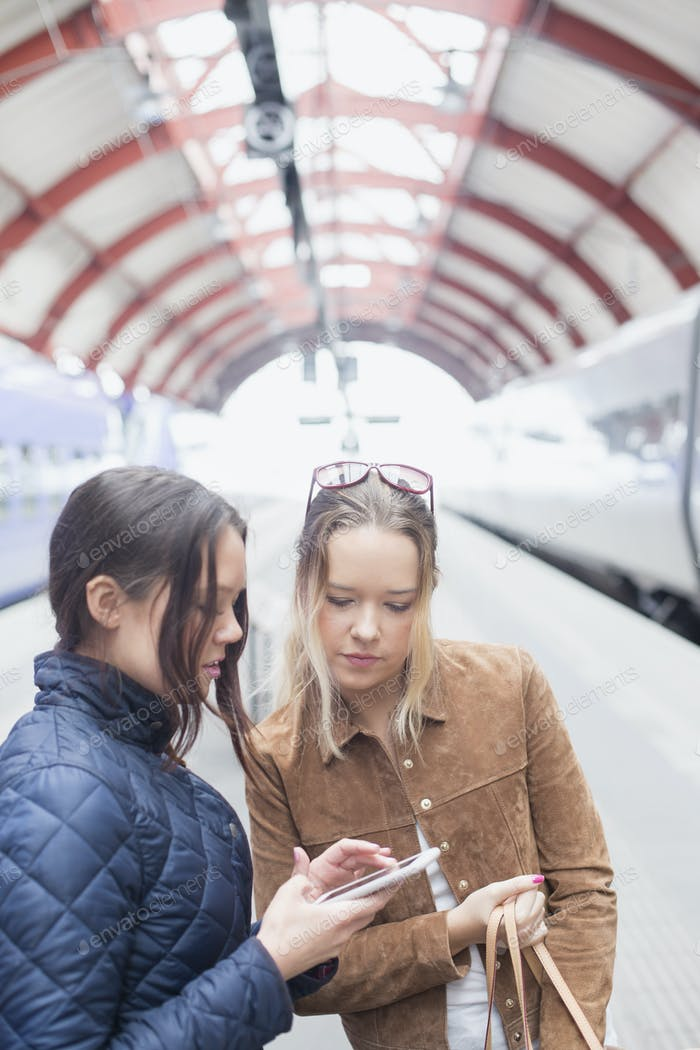 Young women using cell phone at railway station