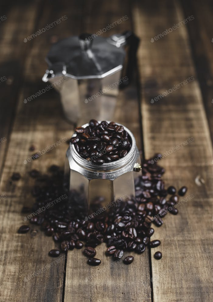 Kaffeebohnen und Mokkakanne auf Holzhintergrund