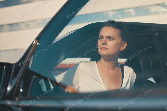 Woman getting down from car searching with eyes for somebody