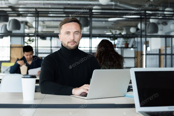 Serious businessman working on project in open space office
