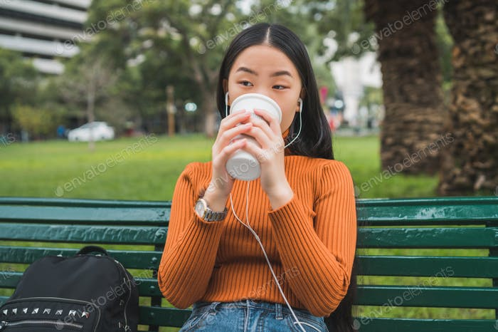 Asian woman listening to music and drinking coffee.