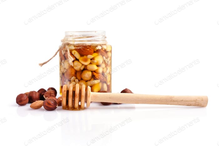 A honey jar with a spoon for honey and different nuts on white b