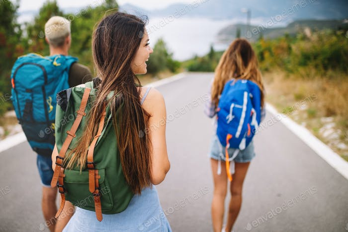 Group of friends backpackers walking and traveling outdoor