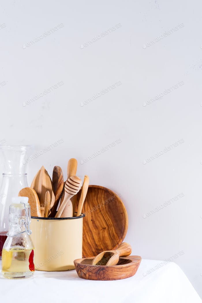 Wooden set of kitchenware in iron cup with wooden plates on white textile table. Cooking appliances