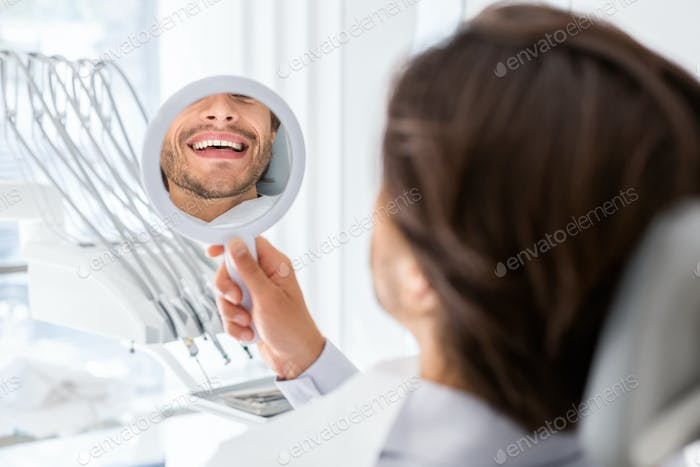 Satisfied patient checking smile at mirror in dental clinic
