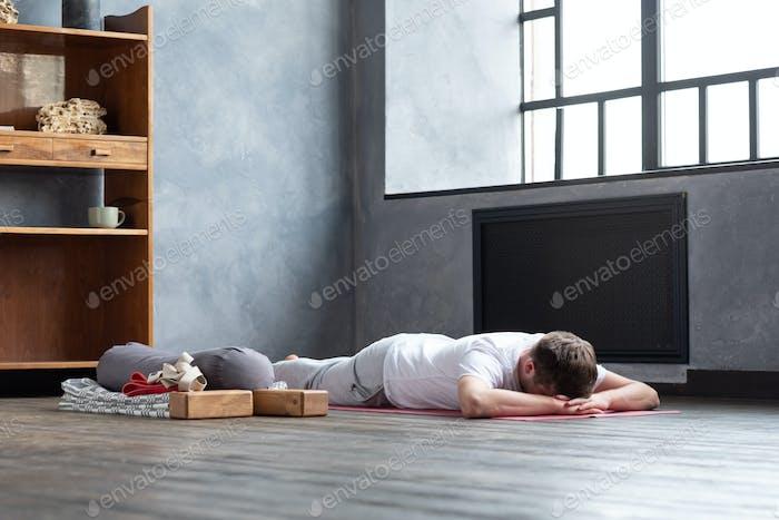 Mann ruht nach Yoga-Praxis auf dem Boden in Makarasana.