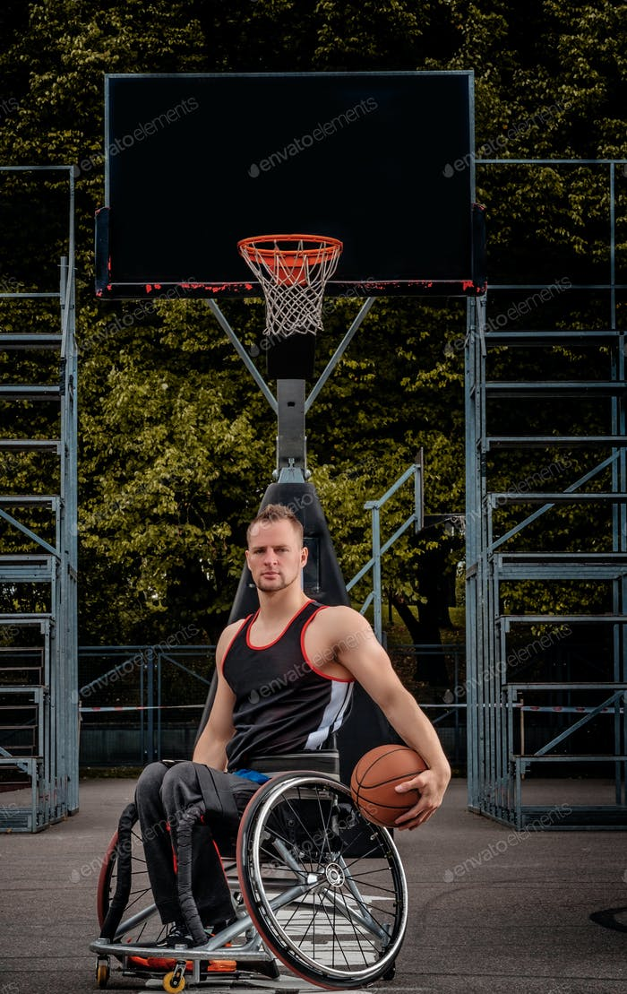 Cripple basketball player in a wheelchair holds a ball on an open gaming ground.