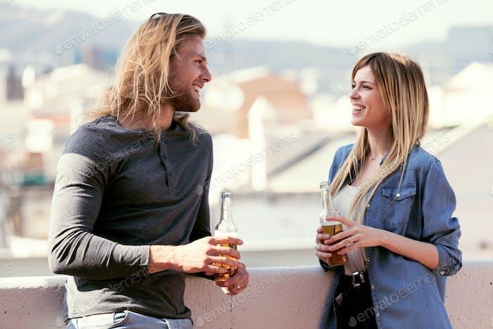Hübsches junges Paar im Gespräch, während Bier auf dem Dach zu Hause trinken.
