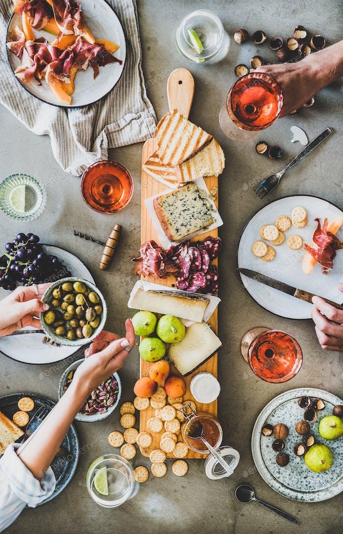 Saisonales Picknick mit Rosenwein, Käse, Wurstwaren und Vorspeisen