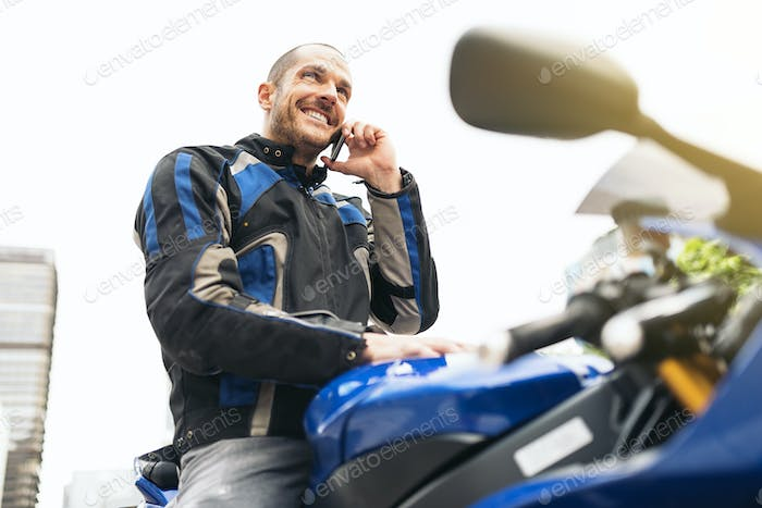 Handsome biker using mobile phone.