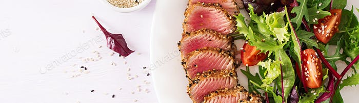 Japanese traditional salad with pieces of medium-rare grilled Ahi tuna and sesame