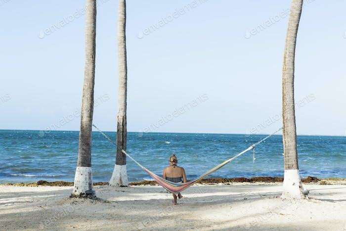 Frau ruht in Hängematte nehmen Bild mit Smartphone, Grand Cayman Island