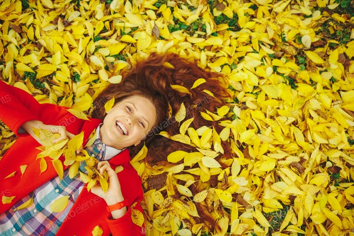 Beautiful happy girl laying in yellow autumn leaves.