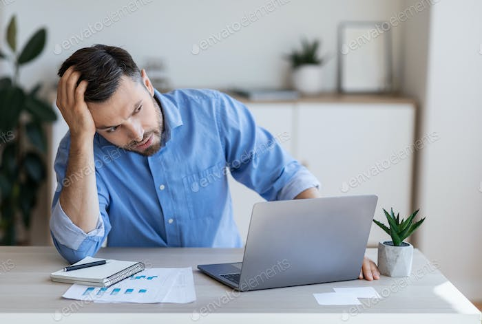 Stressed tired businessman having problems at work, sitting at desk with laptop