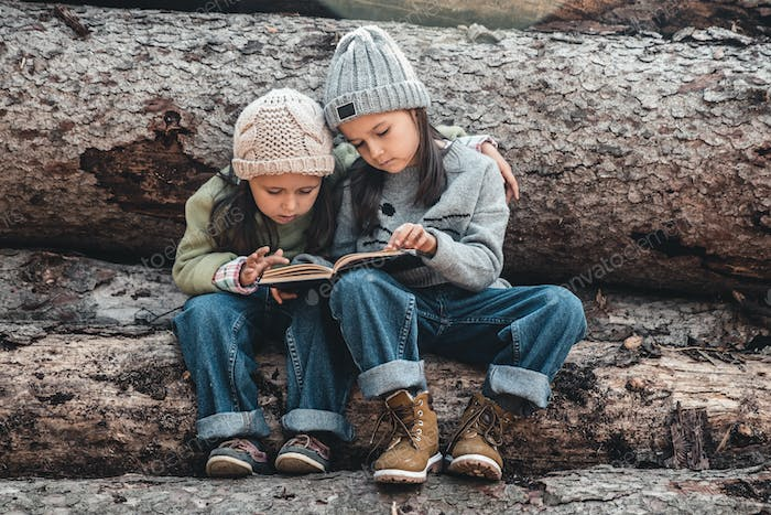 Two little girls reading books, sitting on a log. ?oncept of education and friendship