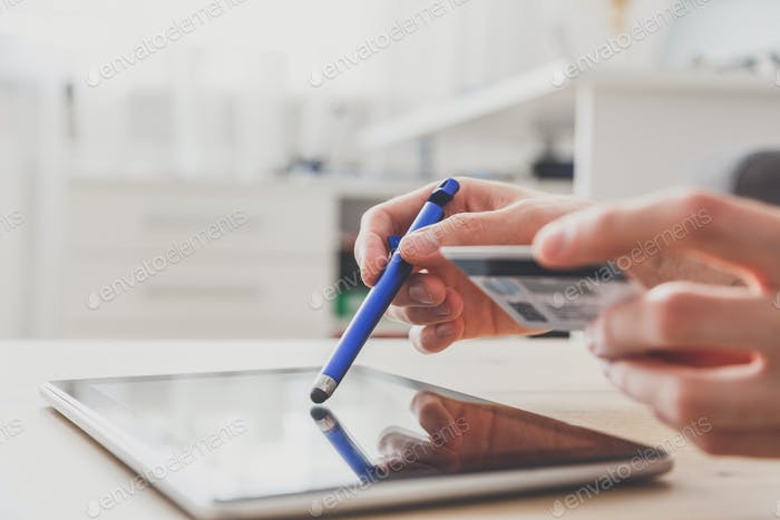 Man using pc tablet with stylus and credit card at the table, shopping online