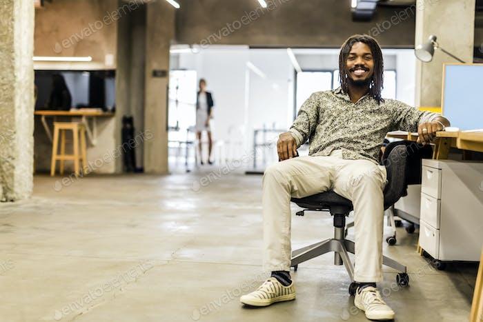 Guapo diseñador de Gráficos sentado en un escritorio