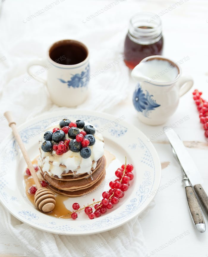 Breakfast set. Buckwheat pancakes with fresh berries, honey, sour cream and cup of coffee