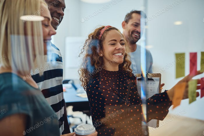 Smiling group of designers brainstorming together in a modern office