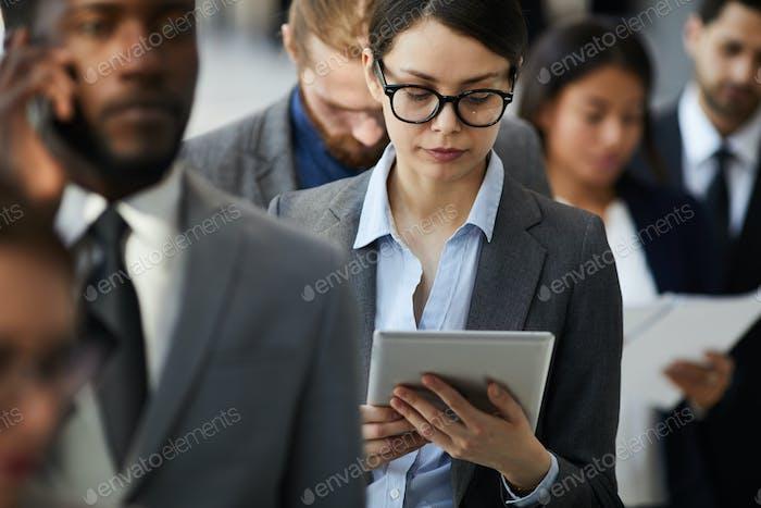 Busy Dame Lesen Dokument auf dem Tablet, während in der Schlange stehen