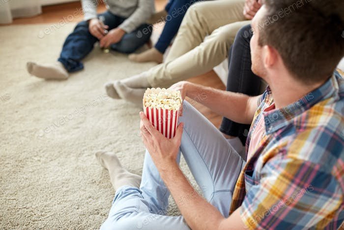 close up of man with friends and popcorn at home