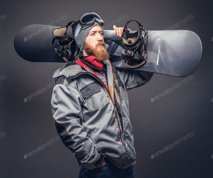 Brutal redhead snowboarder posing with snowboard at a studio. Isolated on the gray background