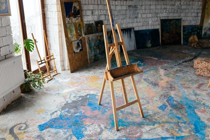 Close up photo of classic wood easel in modern cozy art workshop