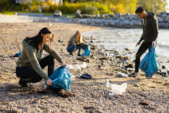 Young woman picking up garbage in bag at beach