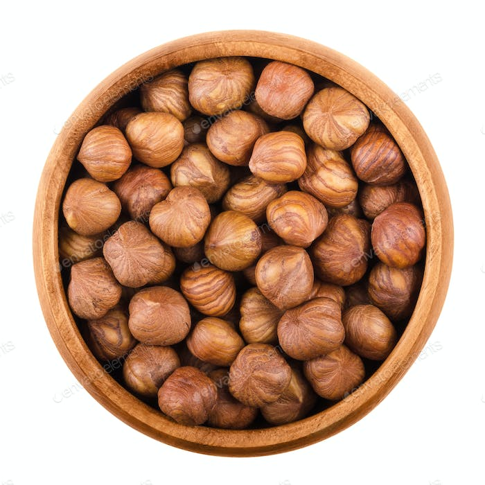 Hazelnuts in a bowl over white