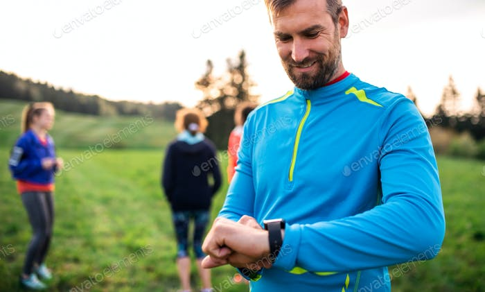 A portrait of man with large group of people doing exercise in nature