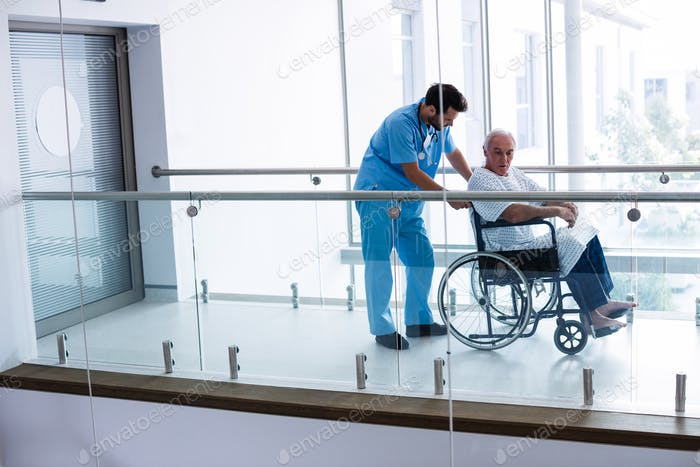 Male doctor pushing senior patient on wheelchair in passageway