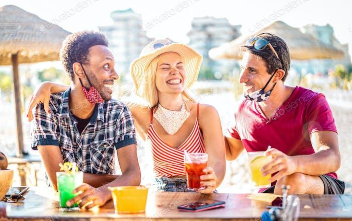 Freundesgruppe trinkt Cocktails am Strand mit offenen Gesichtsmasken